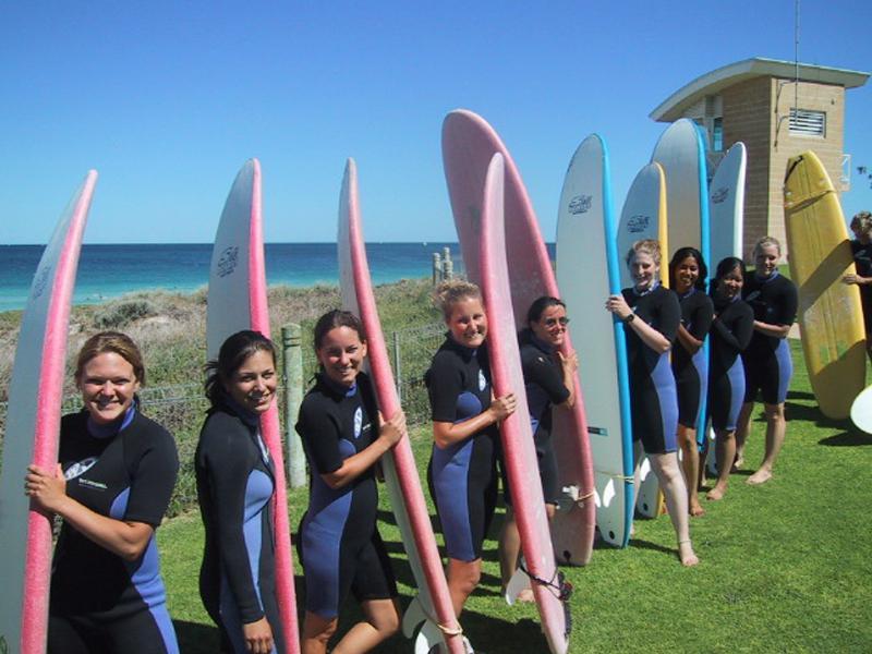 Groupe d'adolescents en bord de mer avec leur planche de surf
