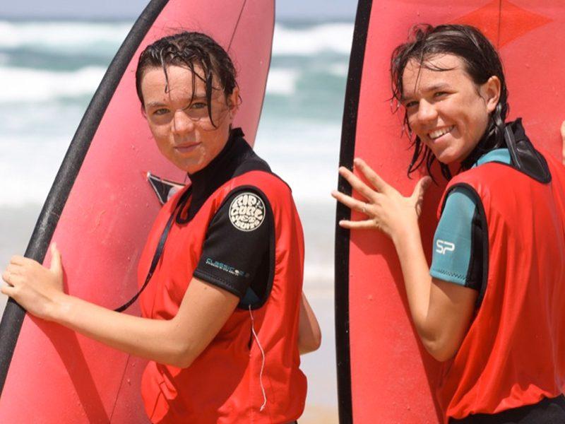 Deux adolescents avec leur planche de surf en colonie de vacances à l'océan