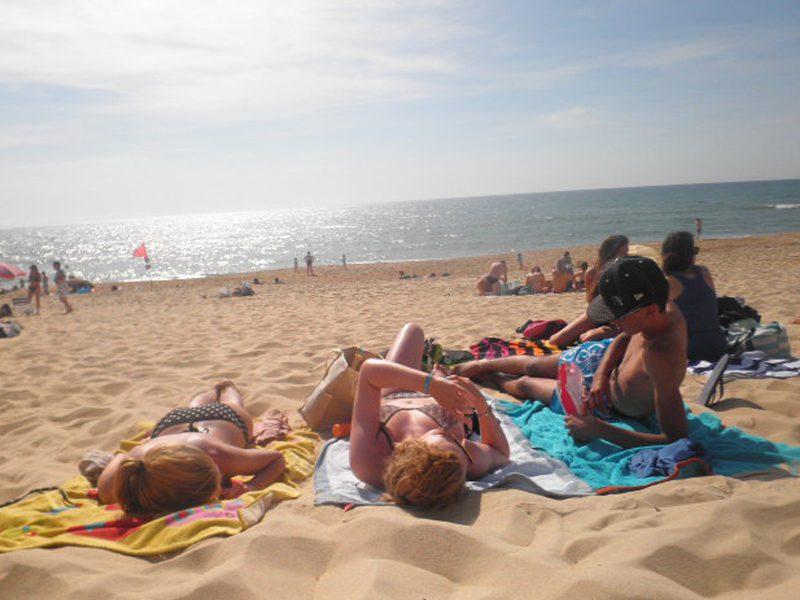 Adolescents qui se font bronzer sur la plage en colo à l'océan