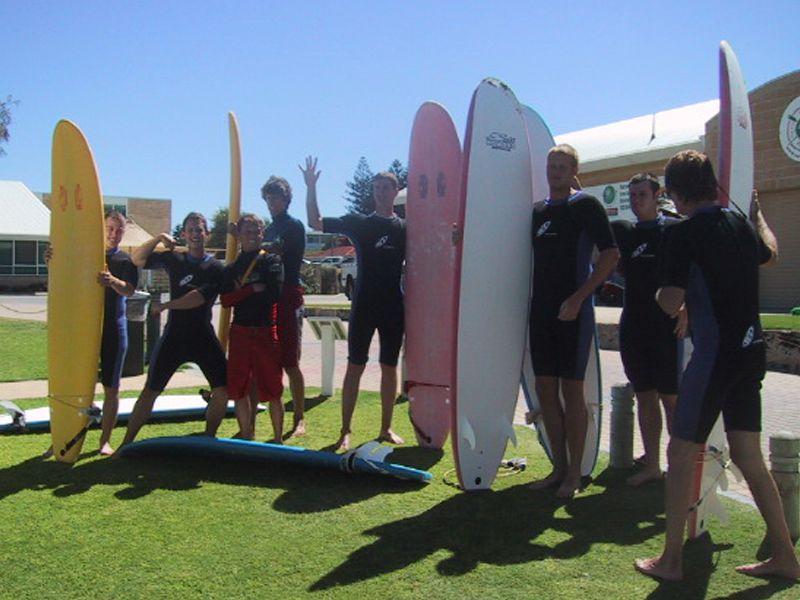 Adolescents sur la page avec leur planche de surf en colonie de vacances pour ados cet été