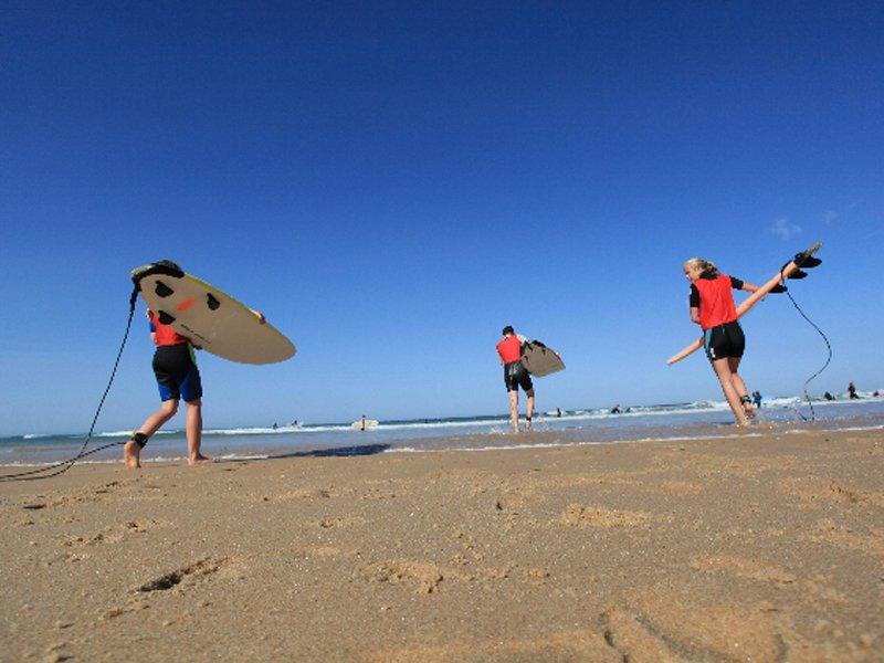 Adolescents rejoignant l'océan avec leur planche de surf cet été en colonie