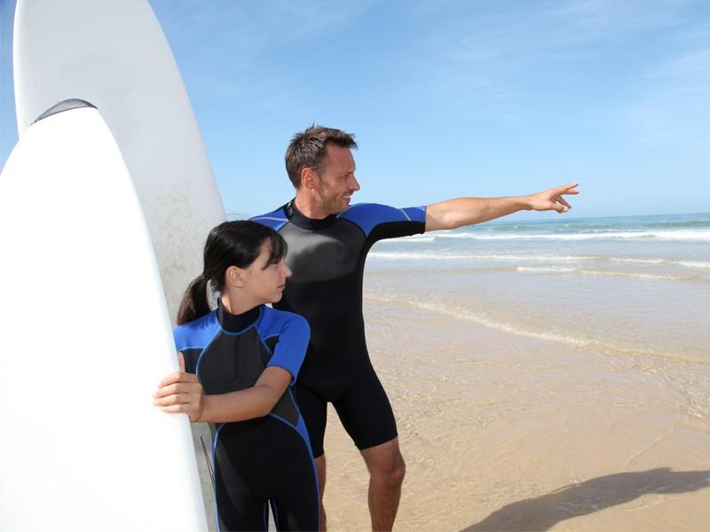 Moniteur de surf montrant l'océan à une adolescente en colonie de vacances surf
