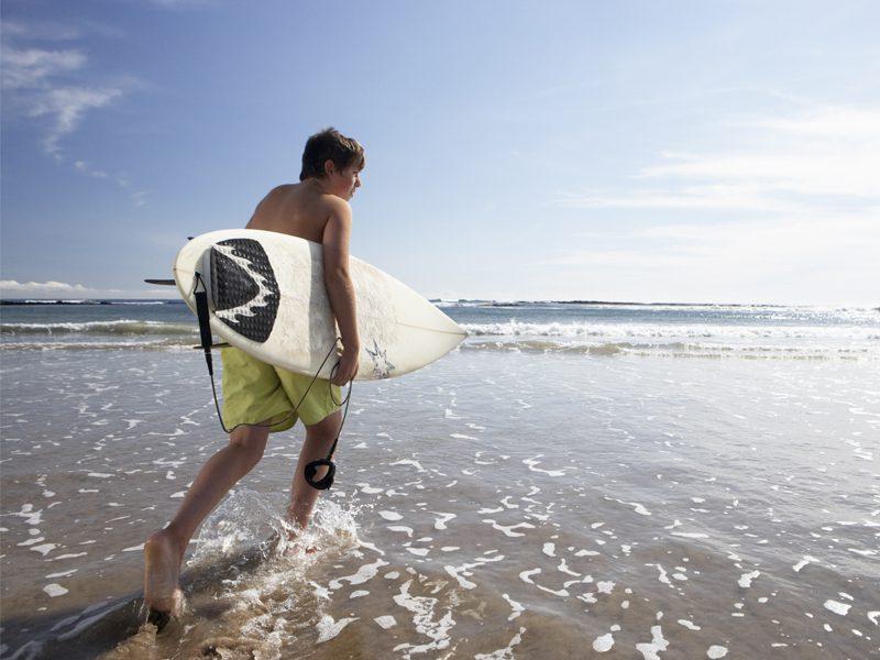Adolescents allant à l'eau avec sa planche de surf en colonie de vacances océan été