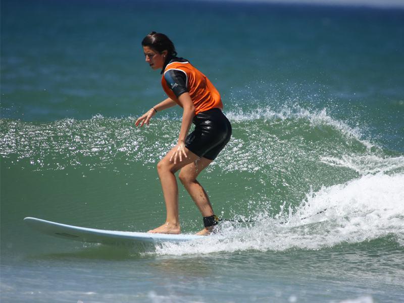 Adolescente faisant du surf à l'océan en colonie de vacances d'été