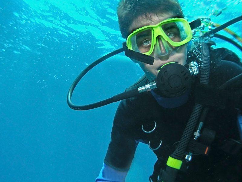 Portrait d'un jeune garçon en plongée sous marine en colonie de vacances pour ados à l'océan