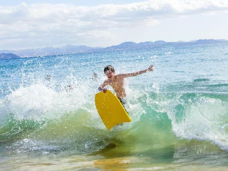Enfant apprenant à faire du surf en colonie de vacances d'été