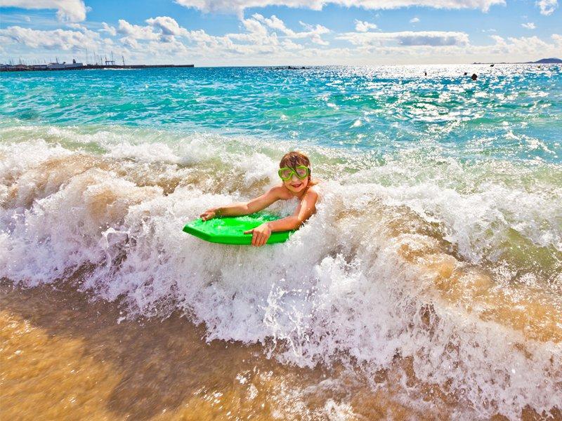 Enfant apprenant à faire du surf en colonie pendant les vacances d'été