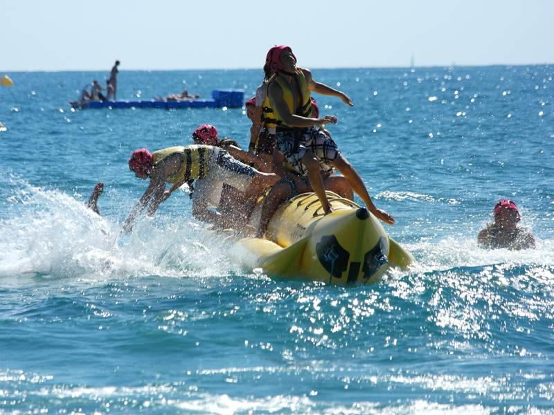 Adolescents sur une bouée tractée en colonie de vacances à l'océan pour ados