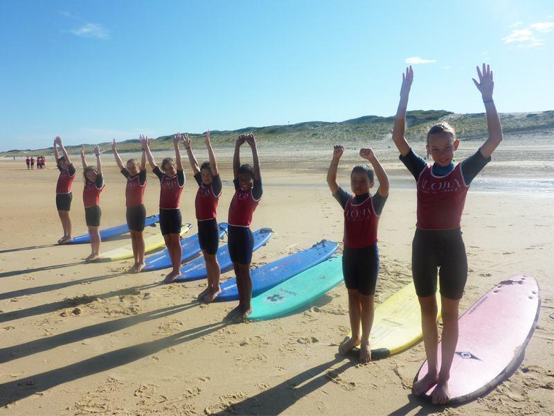 Adolescents faisant des exercices pour apprendre à surfer en colonie de vacances