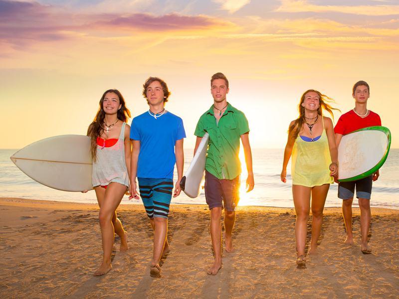 Adolescents marchant à la plage avec leur surf sous le bras en colonie de vacances d'été pour apprendre à faire du surf