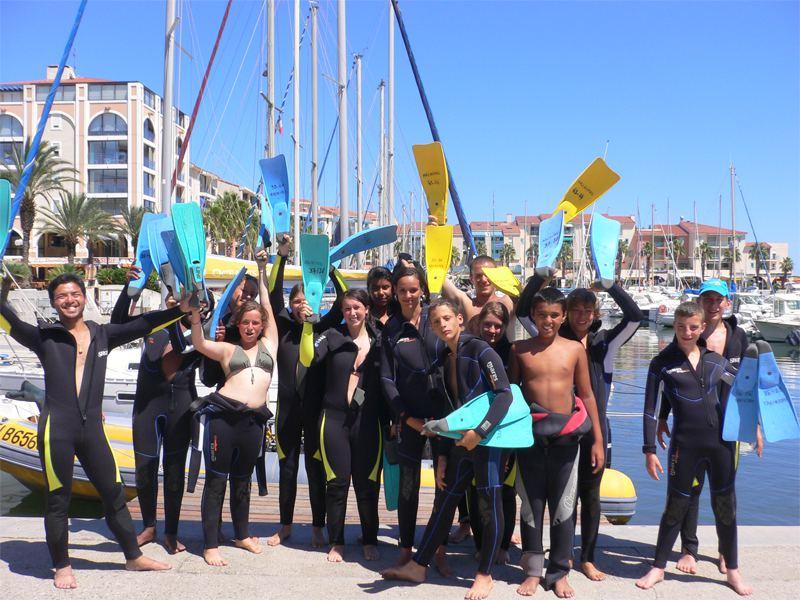 Groupe d'adolescents et leur moniteur en tenue de plongée sous marine en colonie de vacances