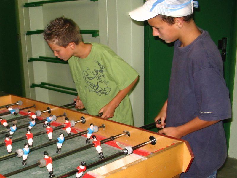 Enfants jouant au baby foot en colo