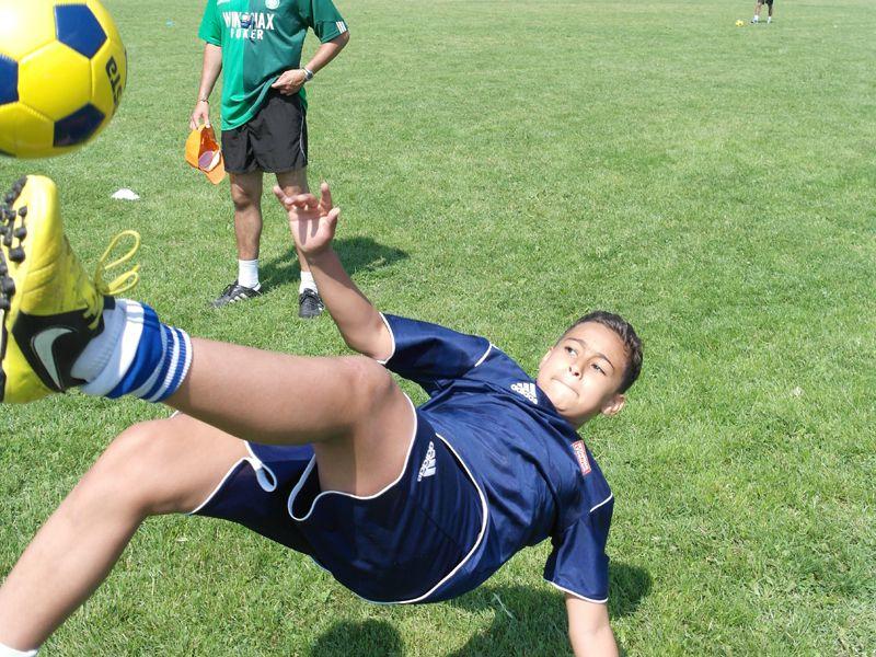 Enfant jouant au football en colonie de vacances d'été