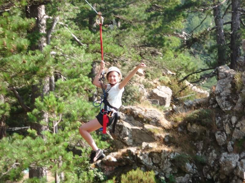 Jeune fille faisant de la tyrolienne en colonie de vacances en Corse