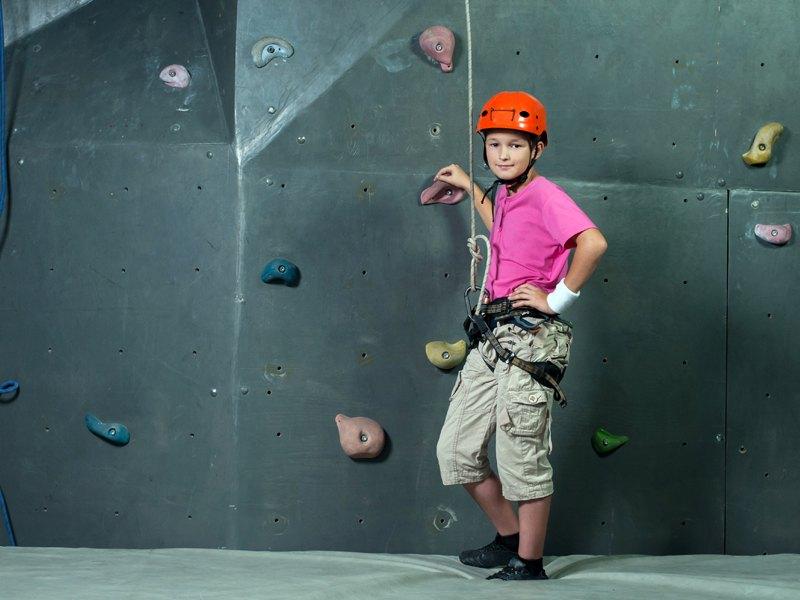 Jeune adolescent posant devant le mur d'escalade en colonie de vacances à Courchevel