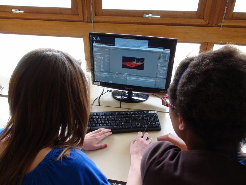 Deux jeunes filles apprenant à faire du montage vidéo en colonie de vacances cinéma été
