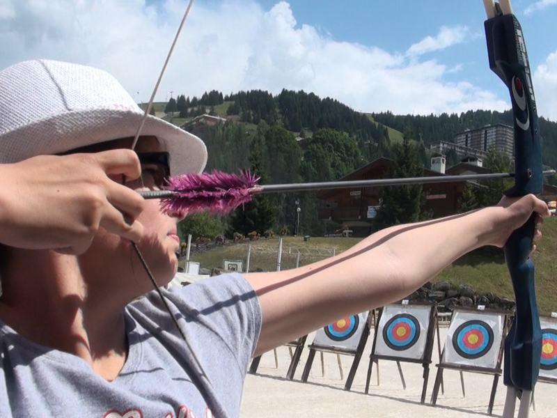 Adolescent visant les cibles avec son arc et ses flèches en colonie de vacances à Courchevel cet été