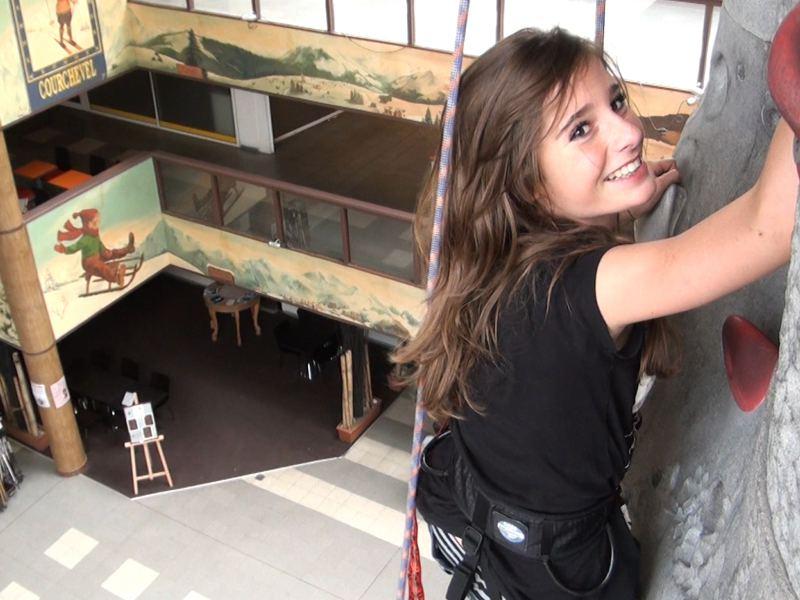 Jeune fille pratiquant l'escalade sur un mur artificiel à Courchevel en colonie de vacances cet été