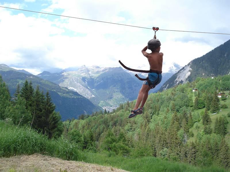 Adolescent faisant de la tyrolienne en montagne cet été en colo