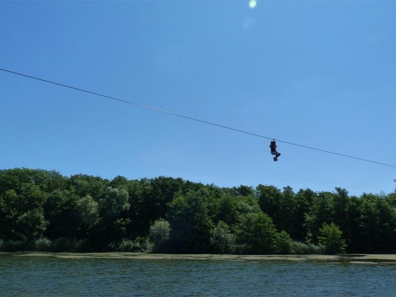 Adolescent faisant de la tyrolienne en colonie de vacances été à la montagne