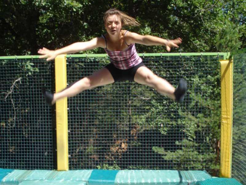 Adolescente faisant du trampoline en colonie de vacances à la montagne