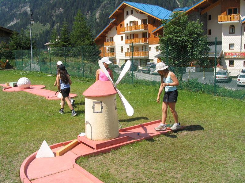 Enfants jouant au mini golf en colonie de vacances à la montagne