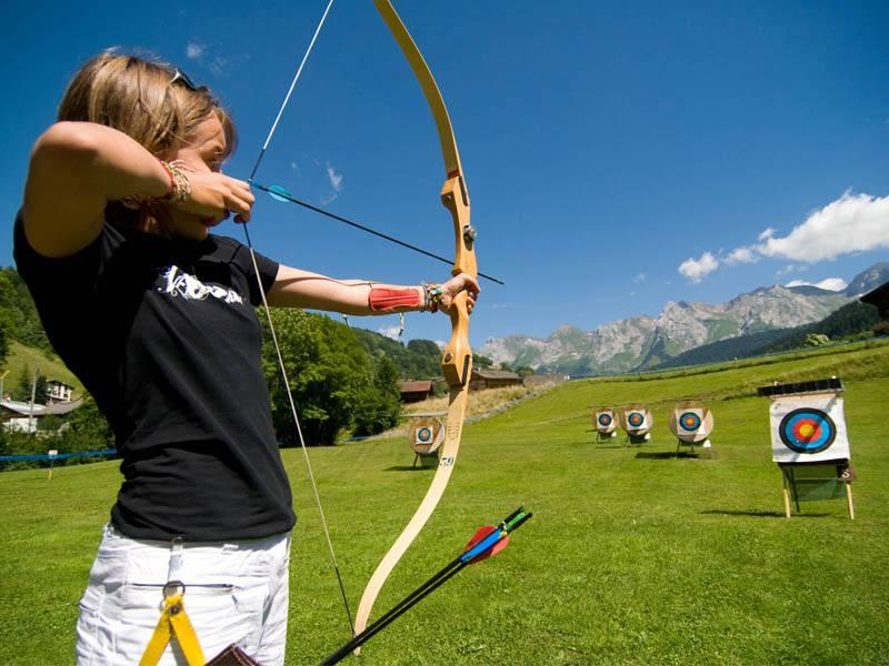 Enfant visant els cibles de tir à l'arc en colonie de vacances à la montagne à Courchevel
