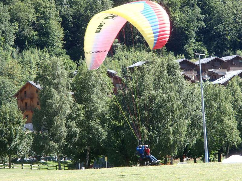 Enfant en plein atterrissage de parapente à Courchevel