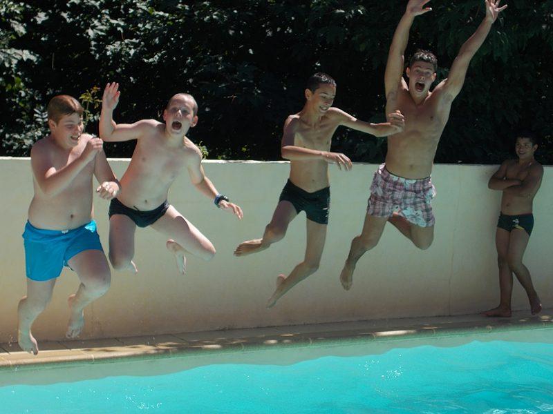 Groupe d'enfants sautant dans la piscine en colonie de vacances à la montagne