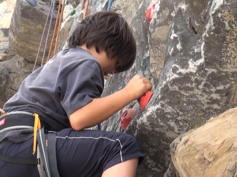 Enfant faisant de l'escalade en colo à la montagne