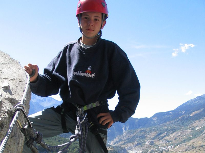 Adolescents en train de faire de la via ferrata en colonie de vaacances à la montagne