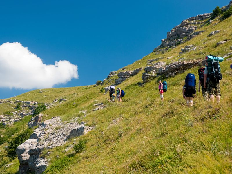 Adolescents et enfants en randonnée à la montagne