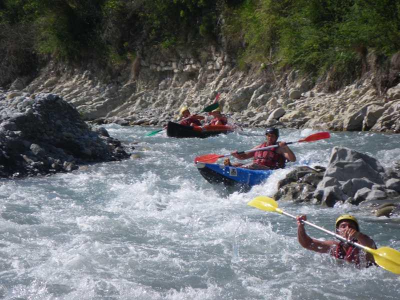 Adolescents et enfants faisant du canoe kayak en colonie de vacances