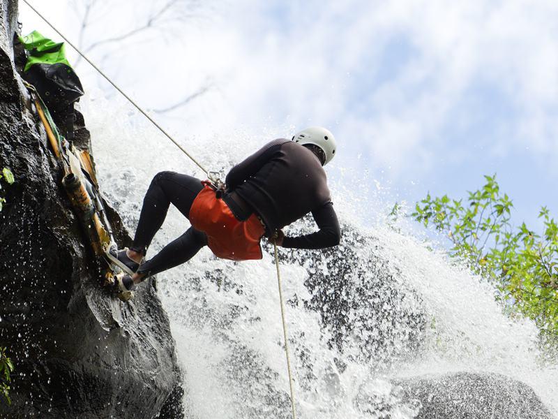 Enfant descendant en rappel contre une cascade en canyoning à Courchevel cet été
