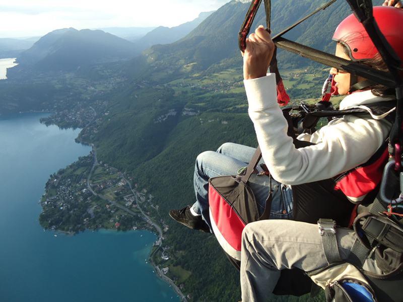 Enfant dans les airs en parapente en colonie de vacances à la montagne