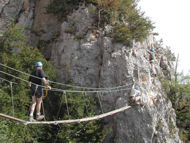 Enfants faisant de la via ferrata en colonie de vacances à la montagne été