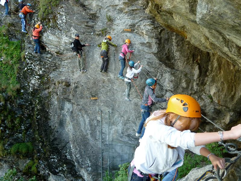 Groupe d'adolescents pratiquant la via ferrata en colonie de vacances d'été à Courchevel