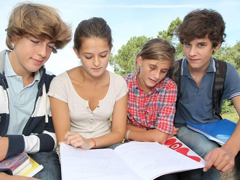 Adolescents travaillant ensemble sur des révisions en colonie de vacances d'été