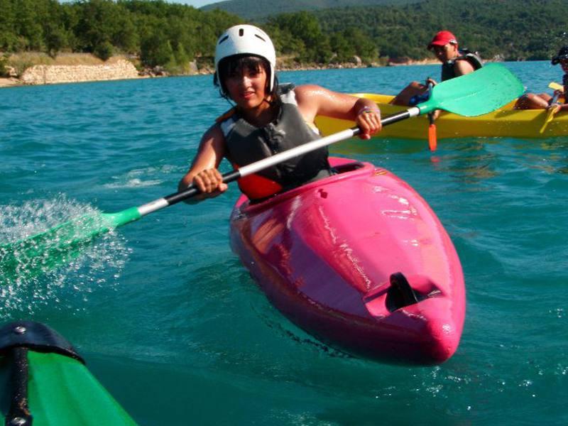 Adolescent faisant du canoe kayak en colo à la montagne