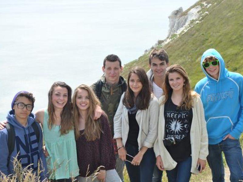 Un groupe d'adolescent devant les falaises du cap Béveziers en Angleterre