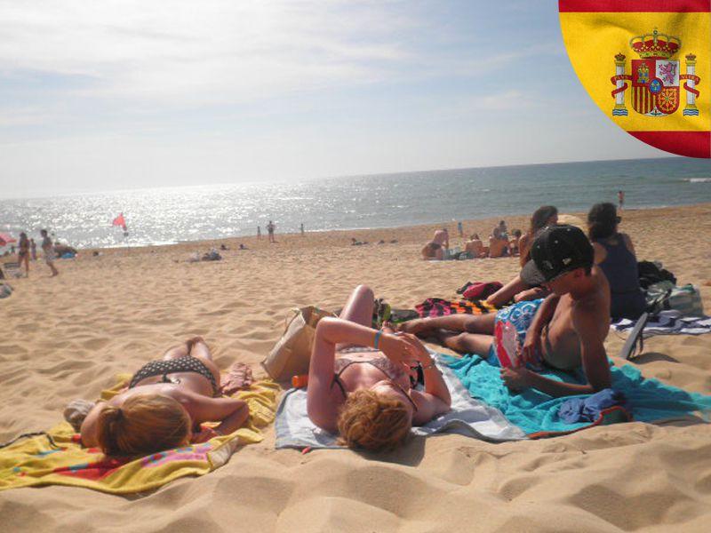 adolescents se faisant bronzer sur la plage en espagne cet été en colonie de vacances