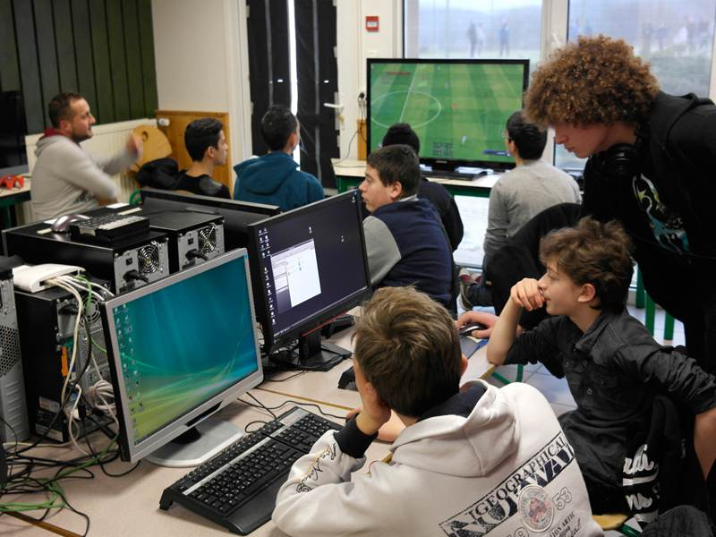 Enfants jouant aux jeux vidéos en colonie de vacances geek