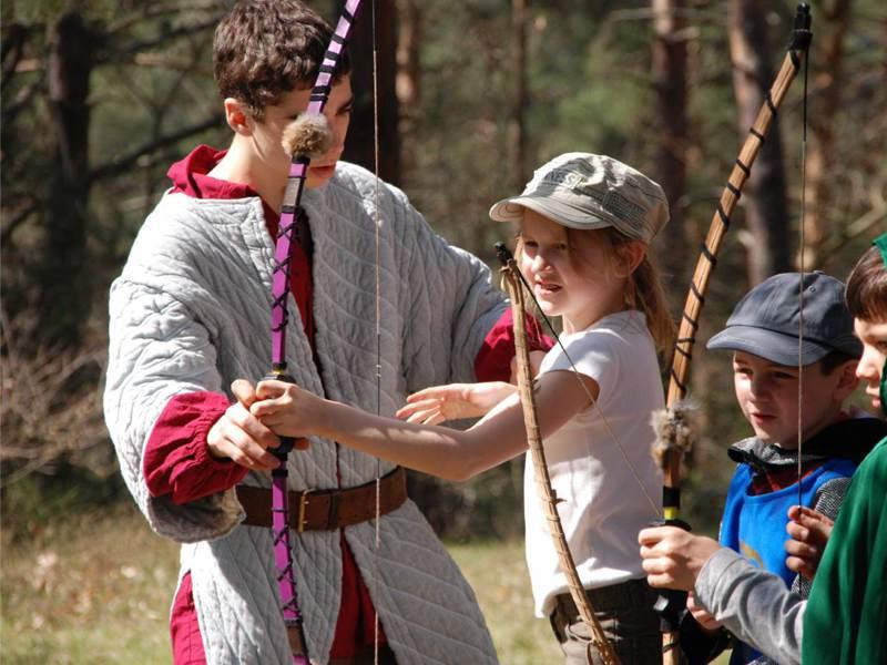 Enfant apprenant à faire du tir à l'arc en colo