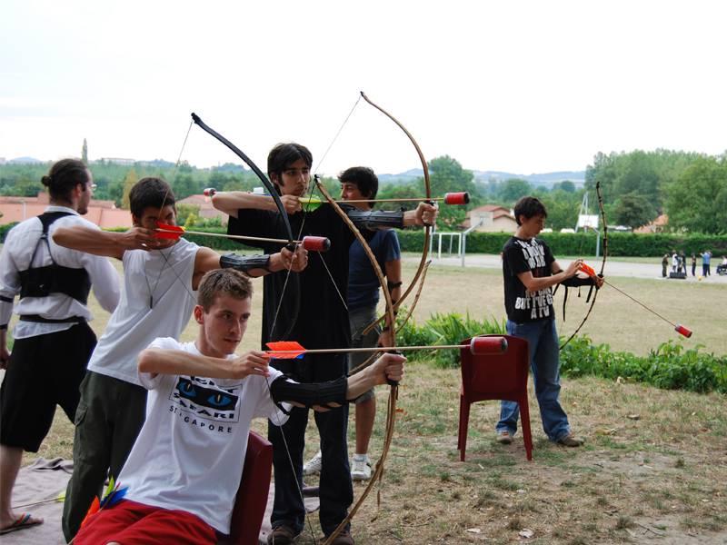 Enfants et ados apprenant à faire du tir à l'arc en colonie de vacances