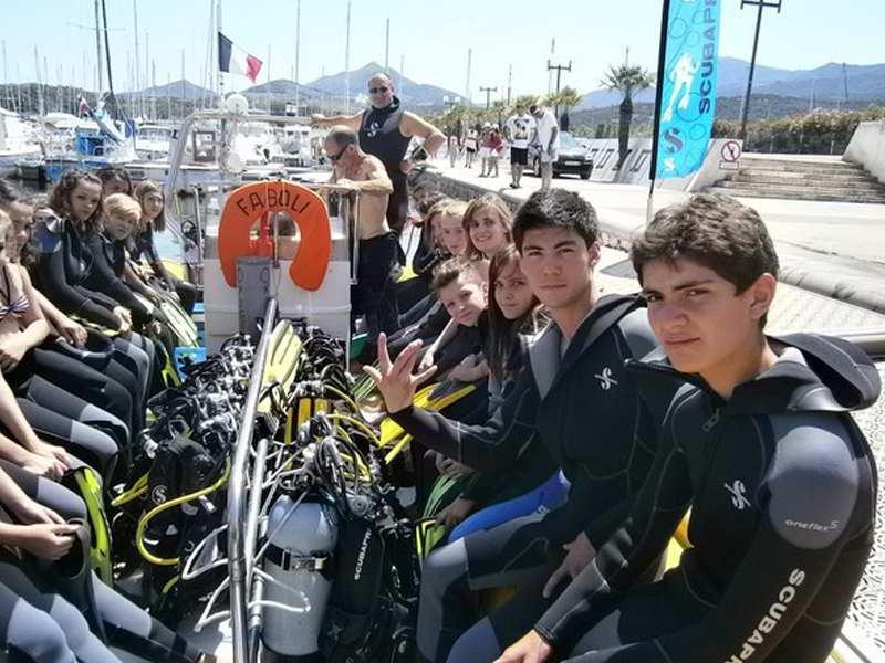 groupe d'ados sur un bateau en tenue de plongee durant une colo