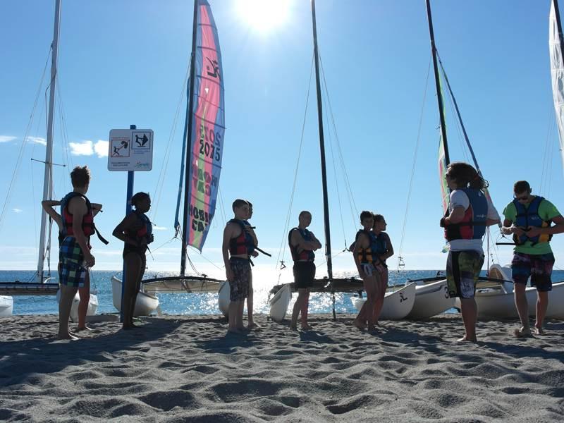 groupe d'ados en bord de mer apprenant à faire du catamaran en colo