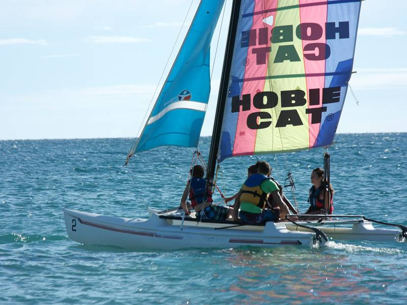 groupe d'ados faisant du catamaran cet été en colonie de vacances a la mer