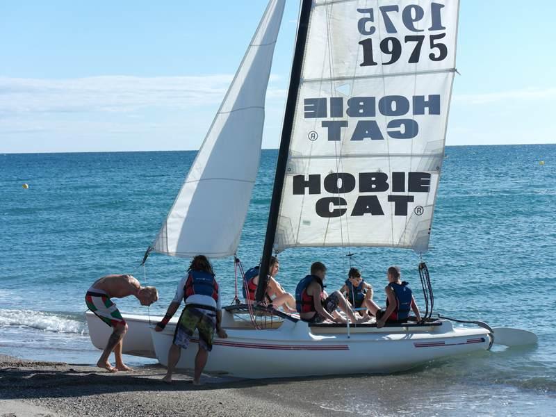groupe d'ados sur un catamaran en bord de mer cet été durant un camp de vacances pour ados a la mer