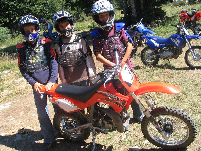 Trois enfants devant leur moto cross en colonie de vacances d'été