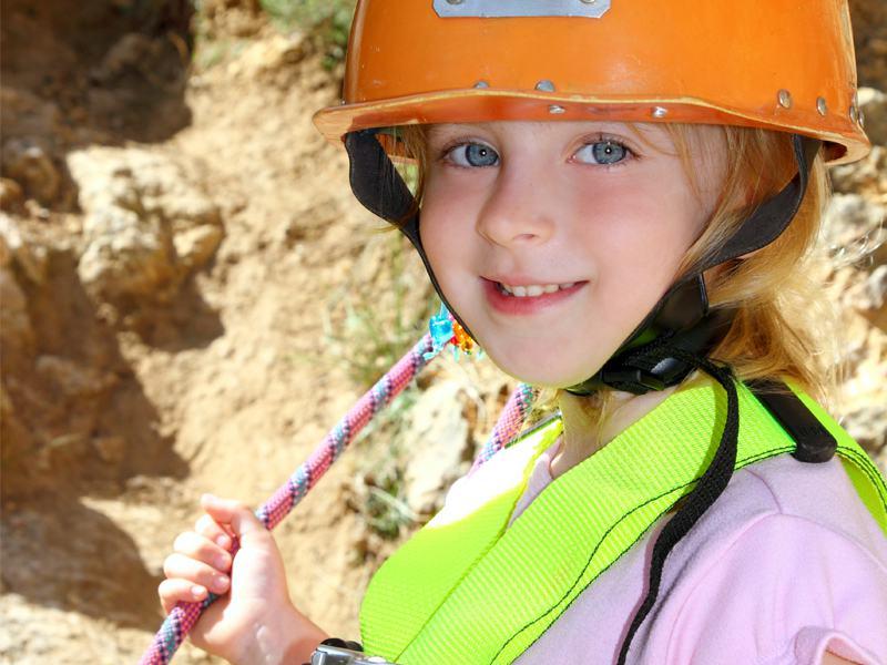 Portrait d'une jeune fille portant un casque pour l'escalade en colonie de vacances d'été